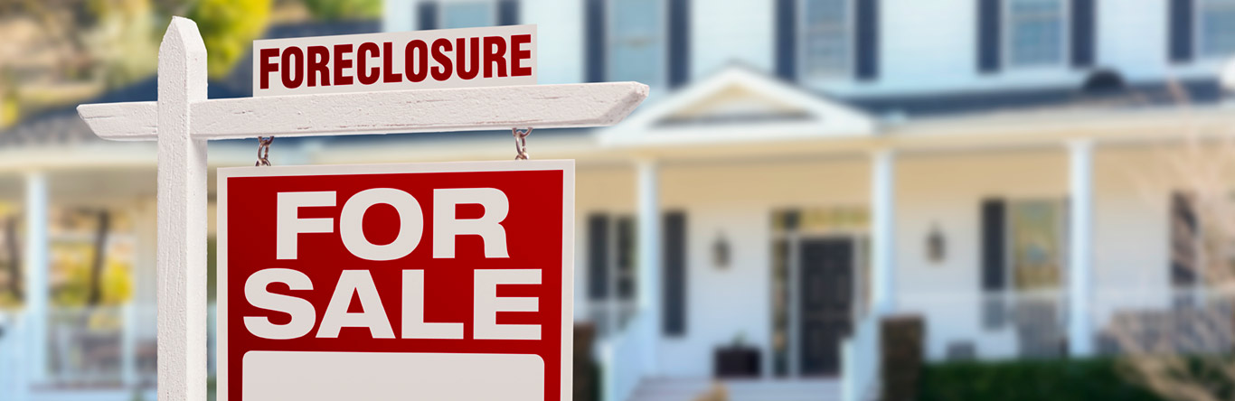 Foreclosure for sale sign in front of house